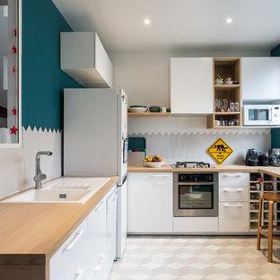 Aménagement d'une cuisine contemporaine en U fermée avec un évier posé, un placard à porte plane, des portes de placard blanches, un plan de travail en bois, une crédence grise, aucun îlot, un sol gris et un plan de travail marron.