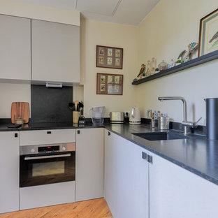 Aménagement d'une cuisine contemporaine en L de taille moyenne avec un évier encastré, un plan de travail en granite, un sol en bois clair, un plan de travail gris, un placard à porte plane et des portes de placard grises.