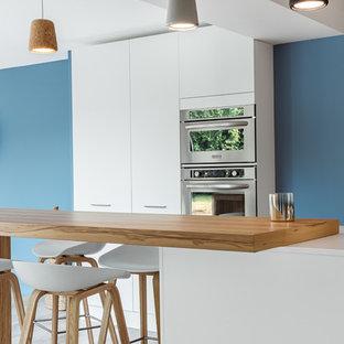Exemple d'une cuisine scandinave avec un placard à porte plane, des portes de placard blanches, un plan de travail en bois et un électroménager en acier inoxydable.