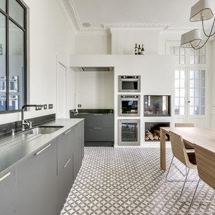 Cette image montre une cuisine américaine design en L avec un évier encastré, un placard à porte plane, des portes de placard grises et un électroménager en acier inoxydable.