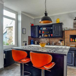 Exemple d'une grand cuisine ouverte linéaire éclectique avec un placard avec porte à panneau surélevé, des portes de placard noires, un îlot central, un sol gris, un plan de travail multicolore, un évier encastré, un plan de travail en carrelage, une crédence métallisée, une crédence en dalle de pierre, un électroménager noir et un sol en vinyl.