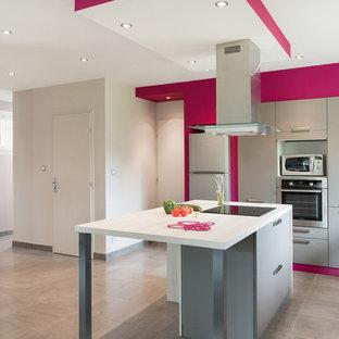 Inspiration pour une cuisine parallèle minimaliste fermée et de taille moyenne avec des portes de placard grises et un îlot central.