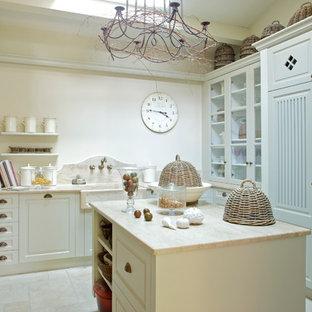 Ejemplo de cocina en L, de estilo de casa de campo, de tamaño medio, cerrada, con puertas de armario blancas, salpicadero beige y una isla