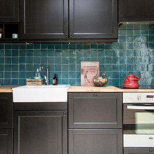 Diseño de cocina lineal, actual, de tamaño medio, abierta, sin isla, con fregadero sobremueble, puertas de armario negras, encimera de madera, salpicadero azul, salpicadero de azulejos de terracota, suelo de madera clara y electrodomésticos de acero inoxidable
