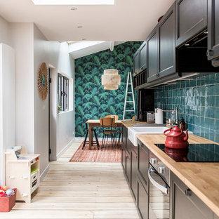 Aménagement d'une cuisine ouverte linéaire moderne de taille moyenne avec un sol en bois clair, un évier 1 bac, un plan de travail en bois, une crédence verte, une crédence en carreau de céramique, un électroménager en acier inoxydable, un placard à porte affleurante et des portes de placard marrons.