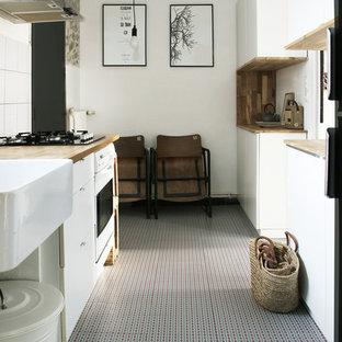 Aménagement d'une cuisine éclectique en U fermée et de taille moyenne avec des portes de placard blanches et un électroménager blanc.