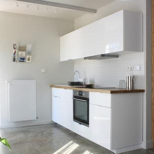 Inspiration pour une cuisine linéaire design avec un évier posé, un placard à porte plane, des portes de placard blanches, un plan de travail en bois, une crédence blanche, béton au sol, un sol gris et un plan de travail marron.