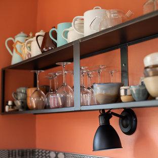 ストラスブールの中サイズのコンテンポラリースタイルのおしゃれなキッチン (シングルシンク、フラットパネル扉のキャビネット、グレーのキャビネット、木材カウンター、黒いキッチンパネル、セメントタイルのキッチンパネル、黒い調理設備、セメントタイルの床、黒い床、茶色いキッチンカウンター) の写真