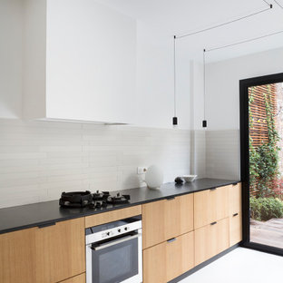 Design ideas for a large contemporary l-shaped eat-in kitchen in Paris with an undermount sink, flat-panel cabinets, beige cabinets, grey splashback, ceramic splashback, panelled appliances, concrete floors, no island, white floor and black benchtop.