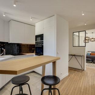 Cette photo montre une petite cuisine scandinave en L avec un évier posé, un placard à porte plane, des portes de placard blanches, une crédence noire, un électroménager noir, une péninsule, un sol gris et un plan de travail blanc.