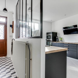 Inspiration for a scandinavian kitchen in Paris with an undermount sink, beaded inset cabinets, grey cabinets, laminate benchtops, black appliances, ceramic floors, a peninsula, grey floor and beige benchtop.