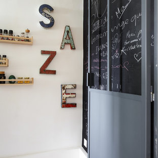 Inspiration for a small scandinavian l-shaped separate kitchen in Paris with a drop-in sink, flat-panel cabinets, black cabinets, wood benchtops, white splashback, ceramic splashback, stainless steel appliances, terrazzo floors, no island, multi-coloured floor and brown benchtop.