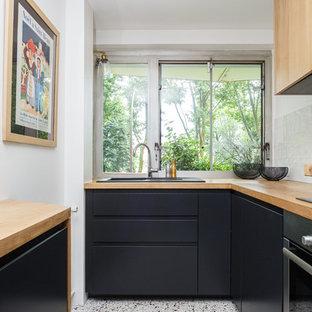 Inredning av ett skandinaviskt litet, avskilt brun brunt l-kök, med en nedsänkt diskho, släta luckor, svarta skåp, träbänkskiva, fönster som stänkskydd, flerfärgat golv, vitt stänkskydd, rostfria vitvaror och terrazzogolv