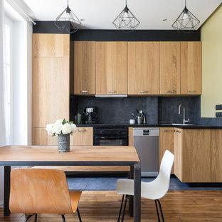 Idée de décoration pour une cuisine américaine design en L avec un placard à porte plane, des portes de placard en bois brun, un électroménager encastrable, un sol en bois brun, aucun îlot, un sol marron et un plan de travail noir.