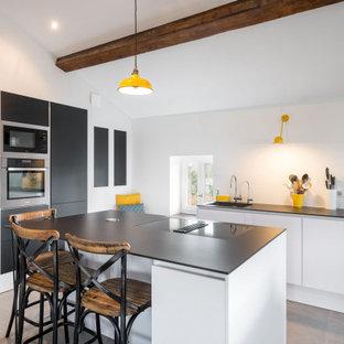 Réalisation d'une cuisine parallèle design de taille moyenne avec un évier 1 bac, un placard à porte plane, une crédence blanche, un électroménager encastrable, un îlot central, un sol gris, un plafond en bois et un plafond en poutres apparentes.