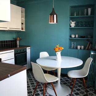 Réalisation d'une petit cuisine américaine design en L avec un placard à porte plane, des portes de placard blanches, un plan de travail en bois, une crédence noire, un électroménager en acier inoxydable, aucun îlot et un sol en carrelage de céramique.