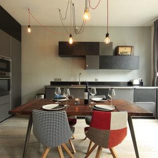 Aménagement d'une grande cuisine américaine contemporaine en L avec un placard à porte plane, des portes de placard grises, un électroménager en acier inoxydable, un sol en bois clair et un évier encastré.