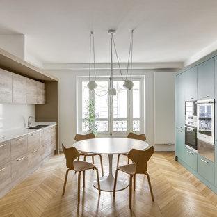 Réalisation d'une cuisine parallèle design fermée avec un évier encastré, un placard à porte plane, des portes de placards vertess, une crédence blanche, un électroménager noir, un sol en bois clair, aucun îlot, un sol beige et un plan de travail blanc.