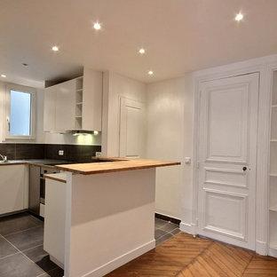 Réalisation d'une cuisine ouverte linéaire victorienne avec des portes de placard blanches, un plan de travail en stratifié, une crédence grise, un électroménager en acier inoxydable, un sol gris et un plan de travail gris.