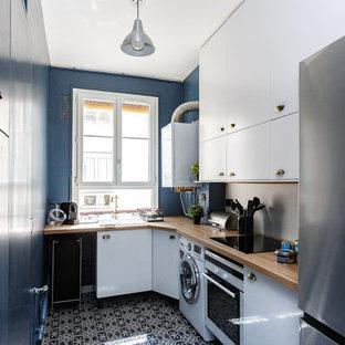 Inspiration pour une cuisine parallèle design fermée avec un évier posé, un placard à porte plane, des portes de placard bleues, un plan de travail en bois, une crédence beige, un électroménager en acier inoxydable, aucun îlot, un sol multicolore et un plan de travail beige.