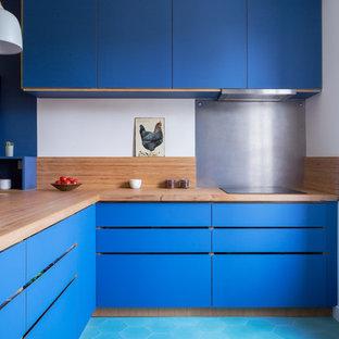 Réalisation d'une cuisine design avec un placard à porte plane, des portes de placard bleues, un plan de travail en bois, une crédence métallisée, un sol turquoise, un plan de travail beige, un évier 1 bac, une crédence en bois, un électroménager de couleur et un sol en carrelage de céramique.