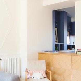 パリの中くらいのコンテンポラリースタイルのおしゃれなキッチン (シングルシンク、フラットパネル扉のキャビネット、青いキャビネット、木材カウンター、メタリックのキッチンパネル、木材のキッチンパネル、カラー調理設備、セラミックタイルの床、ターコイズの床、ベージュのキッチンカウンター) の写真