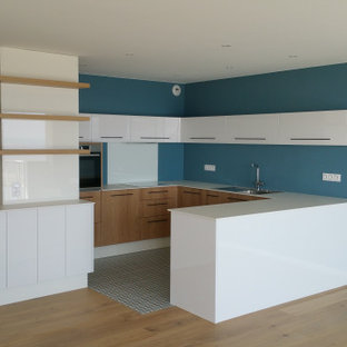 Mid-sized modern u-shaped open plan kitchen in Nantes with an integrated sink, beaded inset cabinets, white cabinets, glass sheet splashback, panelled appliances, cement tiles, with island, blue floor and blue benchtop.