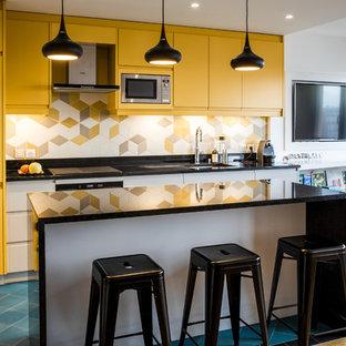 Idée de décoration pour une cuisine ouverte nordique de taille moyenne avec des portes de placard jaunes, une crédence en carreau de porcelaine, un électroménager en acier inoxydable, un sol en carrelage de céramique, un îlot central, un sol bleu, un plan de travail noir, un évier encastré, un placard à porte plane et une crédence multicolore.