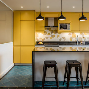 Photo of a mid-sized scandinavian single-wall eat-in kitchen in Paris with a double-bowl sink, yellow cabinets, yellow splashback, porcelain splashback, stainless steel appliances, ceramic floors, with island, blue floor and black benchtop.