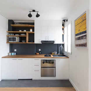 Small modern single-wall eat-in kitchen in Paris with a single-bowl sink, white cabinets, wood benchtops, black splashback, slate splashback, panelled appliances, no island, black floor, brown benchtop, flat-panel cabinets and concrete floors.