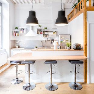 Inspiration pour une cuisine nordique avec un évier posé, un placard sans porte, des portes de placard blanches, un plan de travail en bois, une crédence grise, un électroménager en acier inoxydable, un sol en bois clair et une péninsule.