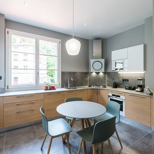 Design ideas for a large contemporary u-shaped separate kitchen in Lyon with an integrated sink, light wood cabinets, quartz benchtops, ceramic splashback, white appliances, ceramic floors, no island, grey floor and flat-panel cabinets.