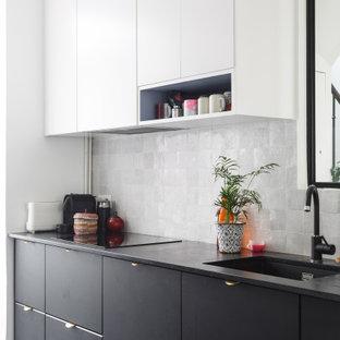 Idée de décoration pour une cuisine nordique avec un évier 1 bac, un placard à porte plane, des portes de placard noires, une crédence grise, un sol gris et un plan de travail noir.