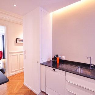Mittelgroße Moderne Wohnküche in U-Form mit integriertem Waschbecken, flächenbündigen Schrankfronten, weißen Schränken, Granit-Arbeitsplatte, Küchenrückwand in Schwarz, Rückwand aus Marmor, braunem Holzboden, Kücheninsel und braunem Boden in Paris