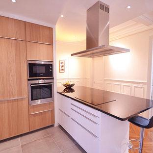 パリの大きいコンテンポラリースタイルのおしゃれなキッチン (フラットパネル扉のキャビネット、中間色木目調キャビネット、御影石カウンター、シルバーの調理設備の、セラミックタイルの床、グレーの床) の写真