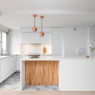 Exemple d'une cuisine tendance en L avec un évier posé, un placard à porte plane, des portes de placard blanches, un électroménager encastrable, une péninsule, un sol gris et un plan de travail blanc.