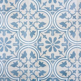 パリの中くらいの北欧スタイルのおしゃれなキッチン (シングルシンク、フラットパネル扉のキャビネット、白いキャビネット、木材カウンター、白いキッチンパネル、セラミックタイルのキッチンパネル、シルバーの調理設備、セメントタイルの床、アイランドなし、青い床、ベージュのキッチンカウンター) の写真