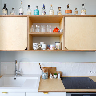 パリの中サイズの北欧スタイルのおしゃれなキッチン (木材カウンター、白いキッチンパネル、ベージュのキッチンカウンター、シングルシンク、フラットパネル扉のキャビネット、白いキャビネット、セラミックタイルのキッチンパネル、シルバーの調理設備の、セメントタイルの床、アイランドなし、青い床) の写真