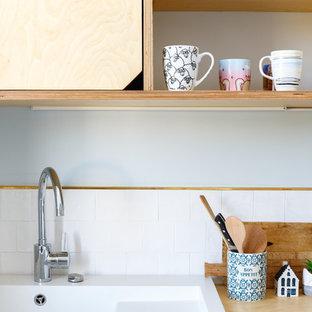 パリの中サイズの北欧スタイルのおしゃれなキッチン (シングルシンク、フラットパネル扉のキャビネット、白いキャビネット、木材カウンター、白いキッチンパネル、セラミックタイルのキッチンパネル、シルバーの調理設備の、セメントタイルの床、アイランドなし、青い床、ベージュのキッチンカウンター) の写真