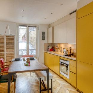 Réalisation d'une cuisine américaine linéaire design avec un évier 1 bac, un placard à porte plane, des portes de placard jaunes, une crédence beige, un électroménager en acier inoxydable, un sol en bois clair, aucun îlot, un sol beige et un plan de travail beige.