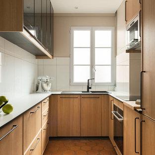 Idée de décoration pour une cuisine américaine tradition avec un évier posé, un placard à porte plane, des portes de placard en bois brun, une crédence blanche, un électroménager encastrable, un sol en carreau de terre cuite, aucun îlot, un sol rouge et un plan de travail blanc.