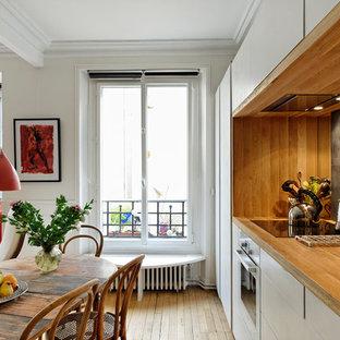 Cette image montre une cuisine ouverte linéaire design de taille moyenne avec un plan de travail en bois, un sol en bois brun, un évier 1 bac, un placard à porte affleurante, des portes de placard beiges, une crédence beige, une crédence en bois, un électroménager en acier inoxydable et 2 îlots.