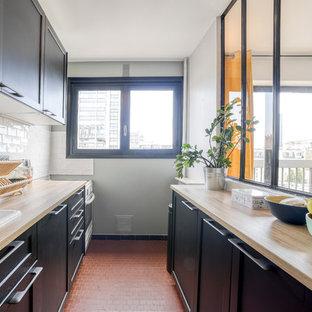 パリのコンテンポラリースタイルのおしゃれなキッチン (ドロップインシンク、黒いキャビネット、ラミネートカウンター、白いキッチンパネル、サブウェイタイルのキッチンパネル、白い調理設備、テラコッタタイルの床、アイランドなし、赤い床、ベージュのキッチンカウンター) の写真