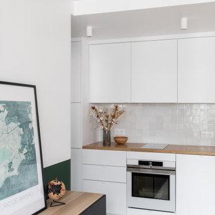 パリの小さいコンテンポラリースタイルのおしゃれなキッチン (シングルシンク、インセット扉のキャビネット、白いキャビネット、木材カウンター、白いキッチンパネル、セラミックタイルのキッチンパネル、白い調理設備、テラゾーの床、マルチカラーの床、ベージュのキッチンカウンター) の写真