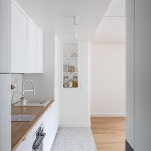 Idéer för små funkis linjära beige kök och matrum, med en enkel diskho, luckor med profilerade fronter, vita skåp, träbänkskiva, vitt stänkskydd, stänkskydd i keramik, vita vitvaror, terrazzogolv och flerfärgat golv