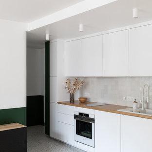 Diseño de cocina comedor lineal, contemporánea, pequeña, con fregadero de un seno, armarios con rebordes decorativos, puertas de armario blancas, encimera de madera, salpicadero blanco, salpicadero de azulejos de cerámica, electrodomésticos blancos, suelo de terrazo, suelo multicolor y encimeras beige