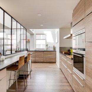 Réalisation d'une cuisine design en L avec un placard à porte plane, des portes de placard en bois clair, un électroménager en acier inoxydable, un sol en bois brun, une péninsule, un sol marron et un plan de travail gris.
