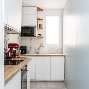 Exempel på ett avskilt, litet modernt beige beige l-kök, med en nedsänkt diskho, släta luckor, vita skåp, träbänkskiva, vitt stänkskydd, stänkskydd i marmor, rostfria vitvaror, klinkergolv i keramik och grått golv