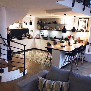 Inspiration för mellanstora minimalistiska brunt kök, med vita skåp, träbänkskiva, vitt stänkskydd, stänkskydd i terrakottakakel, rostfria vitvaror, en köksö, en undermonterad diskho, släta luckor, cementgolv och grått golv