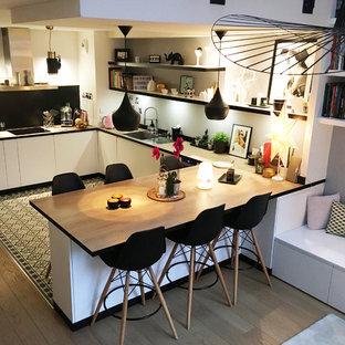 На фото: п-образная кухня-гостиная среднего размера в скандинавском стиле с белыми фасадами, деревянной столешницей, белым фартуком, фартуком из терракотовой плитки, техникой из нержавеющей стали, островом, врезной раковиной, плоскими фасадами, полом из цементной плитки, серым полом и коричневой столешницей с